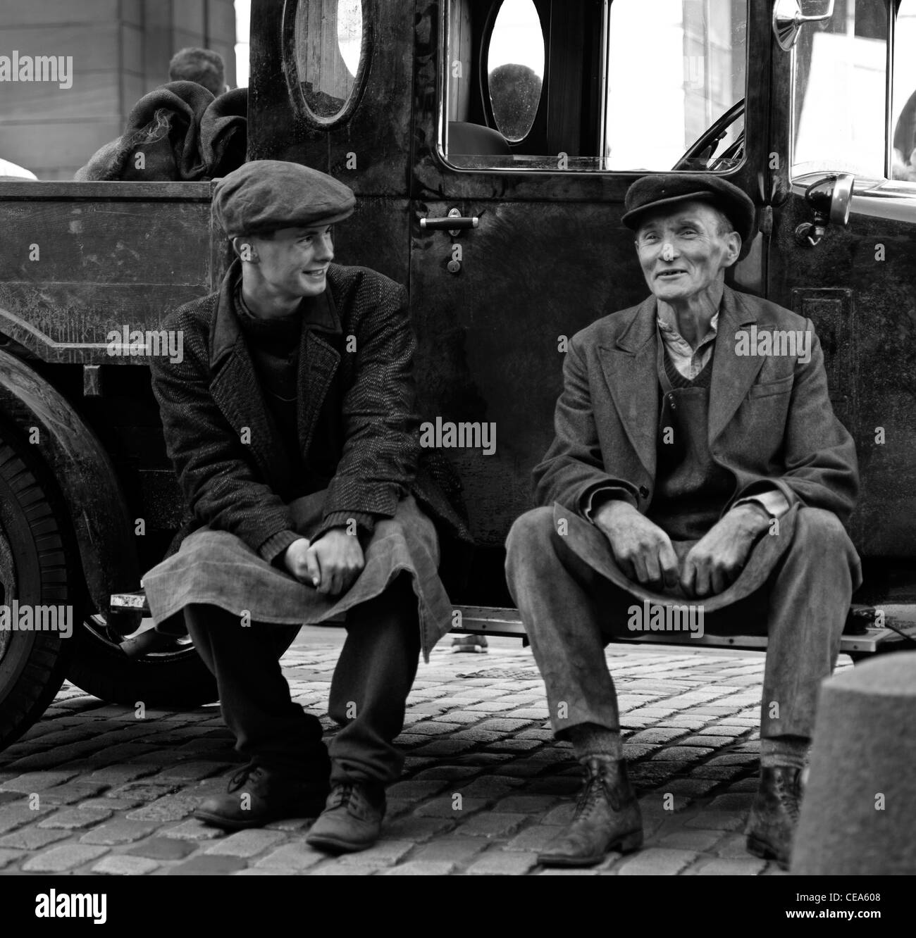 Man and boy in vintage outfits dressed as coalmen sitting on step of old fashioned truck Edinburgh Scotland UK monochrome - Stock Image
