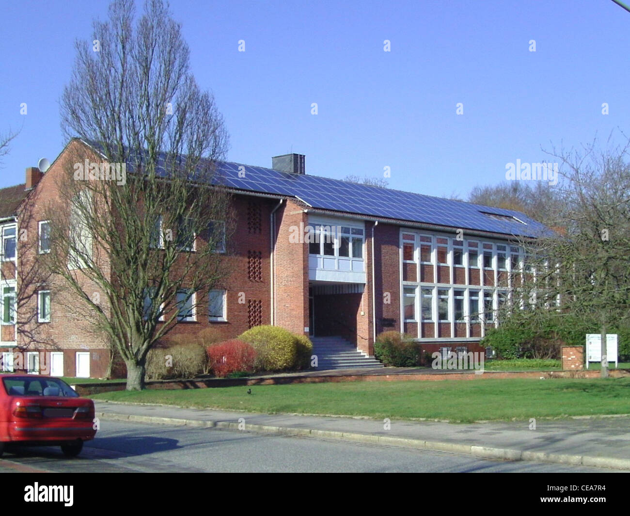 Building with solar panels on the roof in Northern Germany - Stock Image