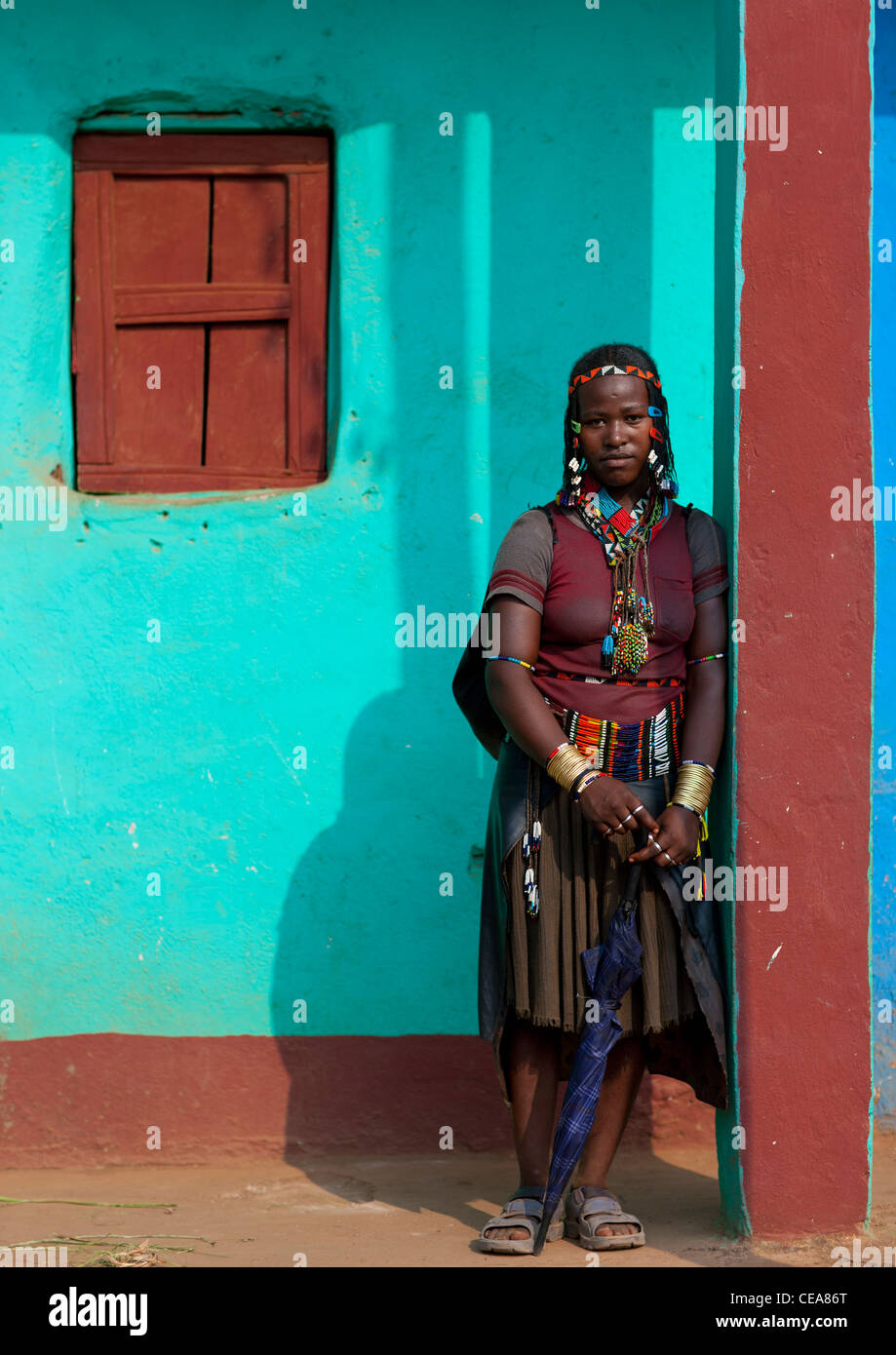 Traditional Clothing Ara Woman Posing Outside Of Blue House In Jinka Omo Valley Ethiopia - Stock Image