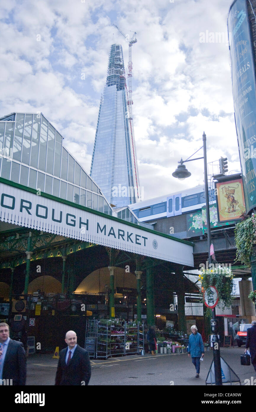 The Shard construction building giant crane towering over the Borough Market sign & canopy & new train bridge - Stock Image