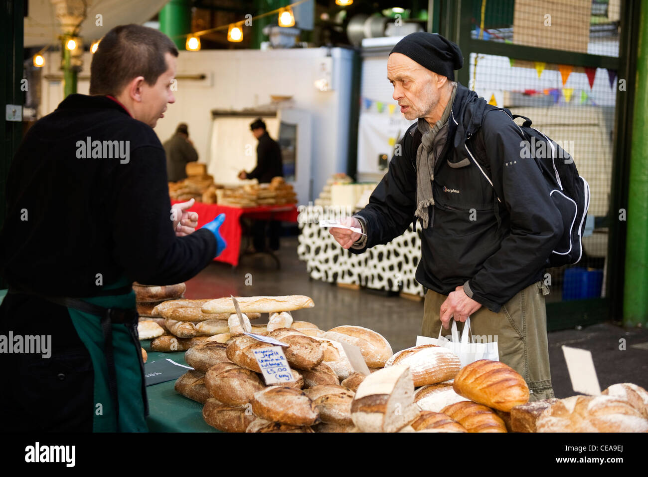 Borough Market London eccentric skinny old man male in woolly hat scarf & rucksack buying freshly baked bread - Stock Image