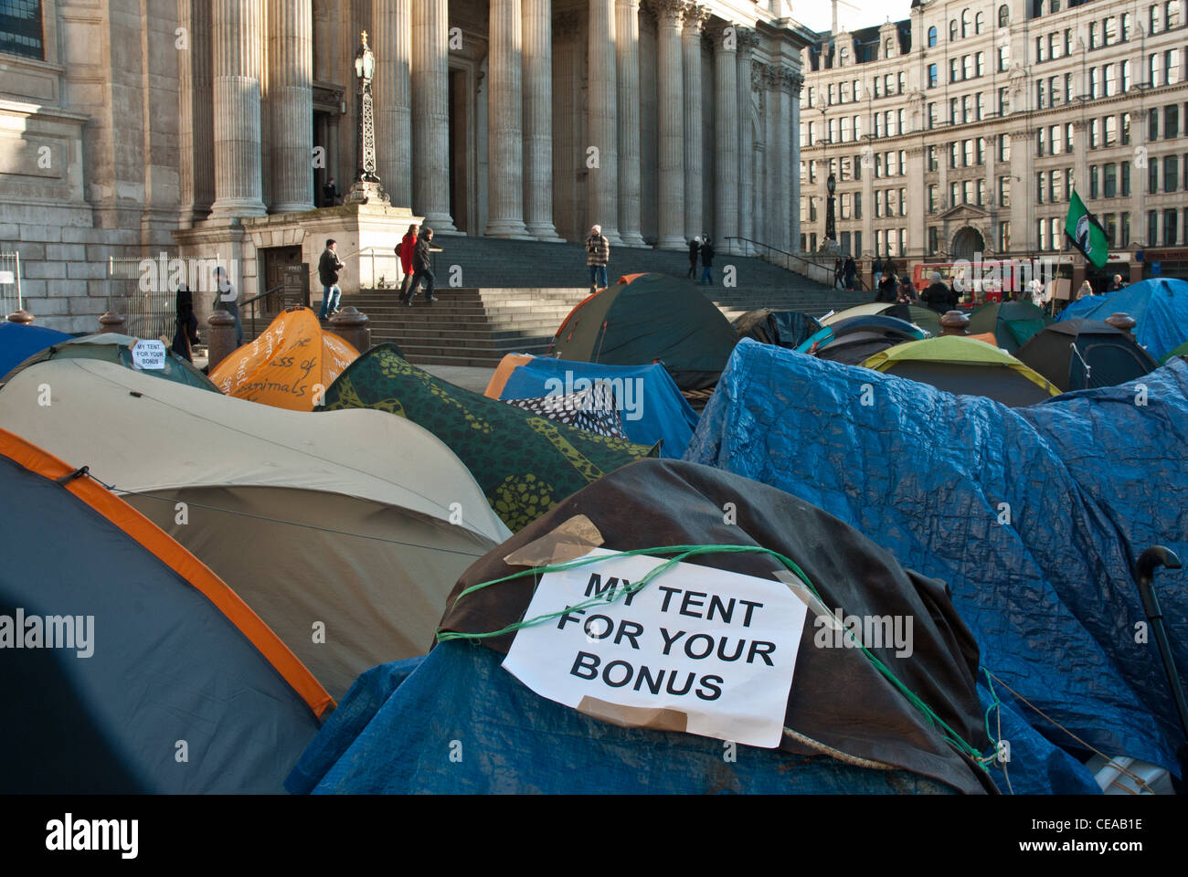 Occupy London, St Pauls. Tents in front of cathedral with placard 'my tent for your bonus' in foreground. - Stock Image