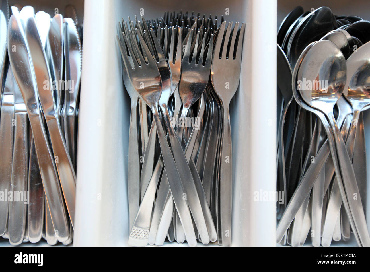 Sorted cutlery with spoons, knives and forks - Stock Image