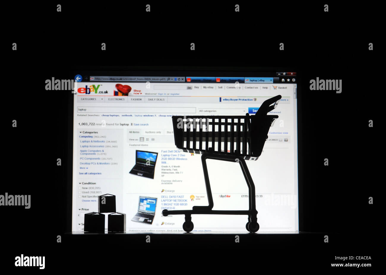 COMPUTER SCREEN WITH SHOPPING TROLLEY PARCELS RE INTERNET SHOPPING EBAY  ONLINE BUYING BUYERS FRAUD INCOME  ECONOMY - Stock Image