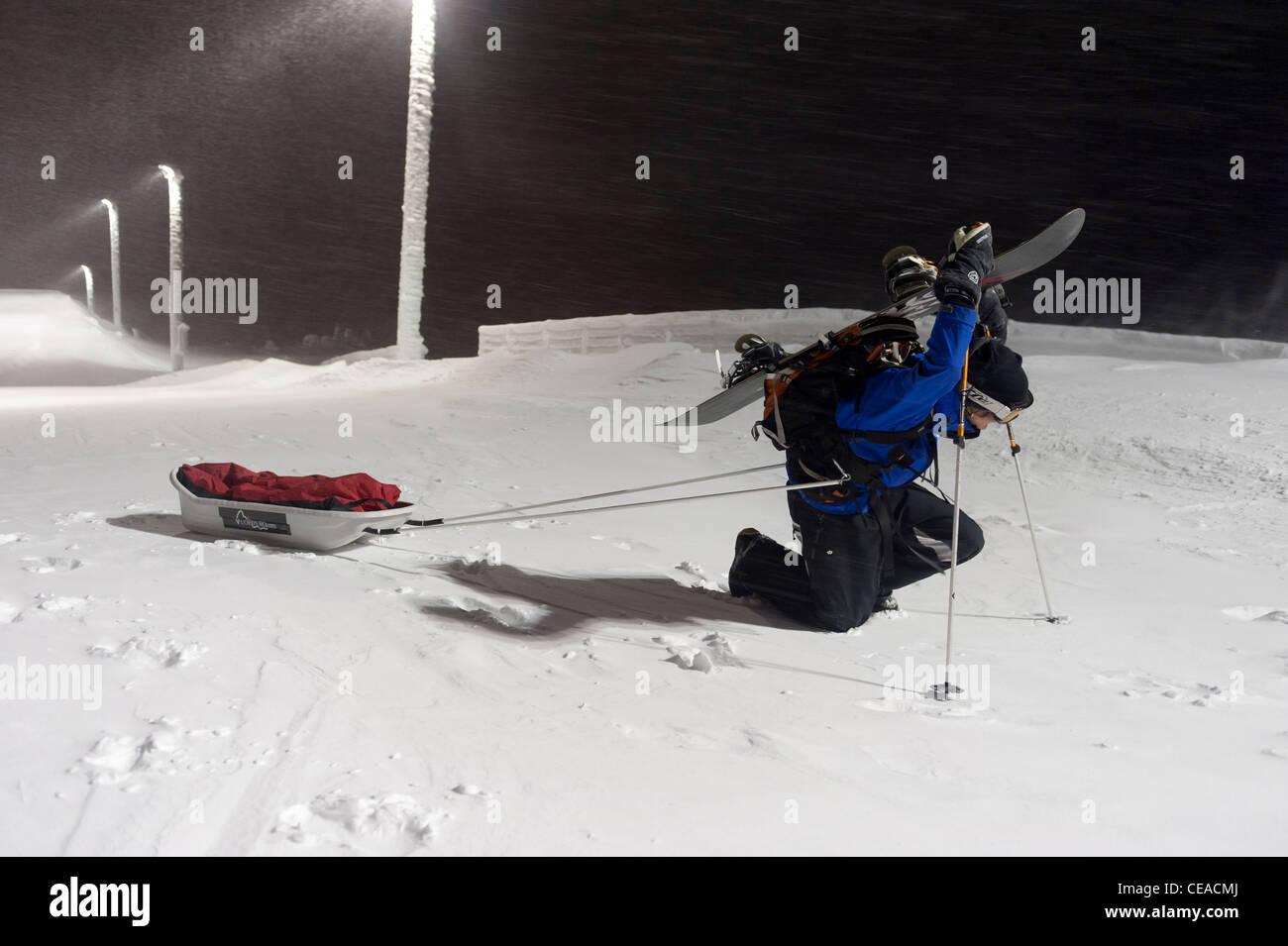 A nowboarder exercising sledge pulling up the slope of Pyhätunturi, Finnish Lapland. - Stock Image