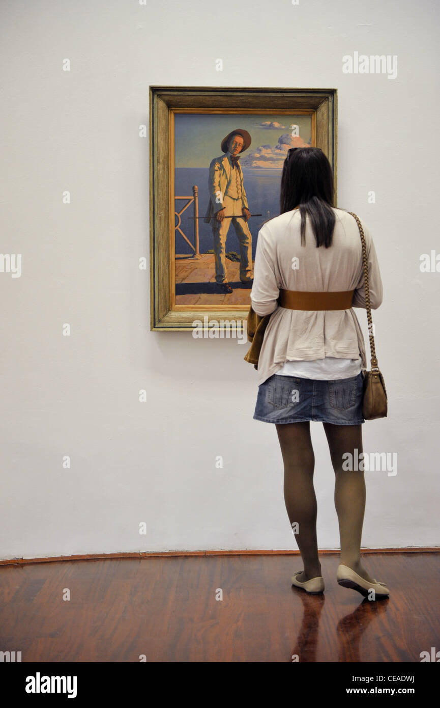 Girl looking at a painting in gallery. - Stock Image