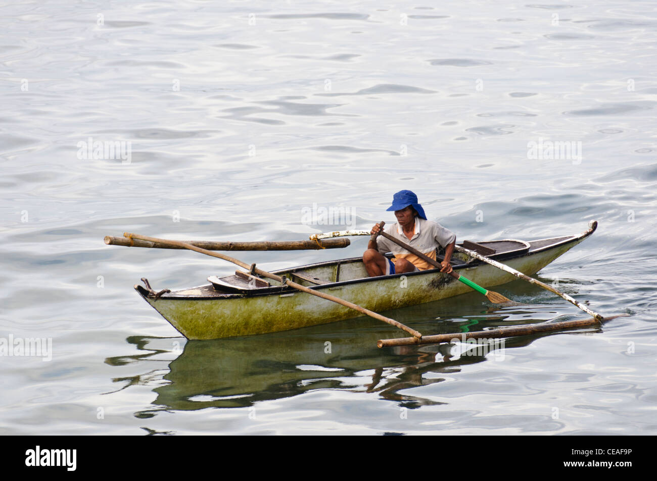 Old Asian man with blue cap rowing a small Philippine outrigger boat, also  called banca or banka in the ocean