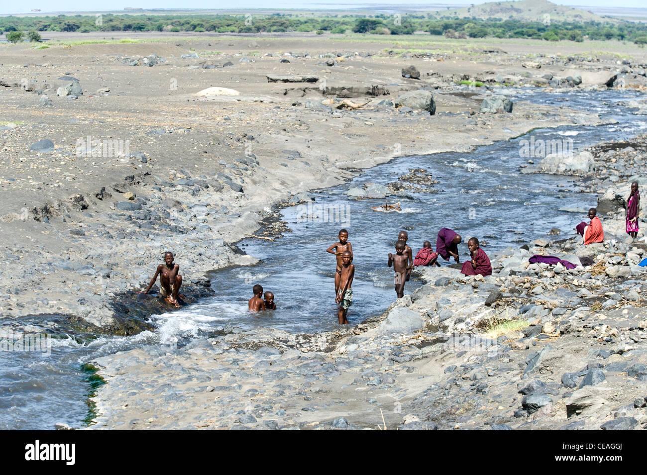 Maasai children bathing in a river at Engaresero in northern Tanzania - Stock Image