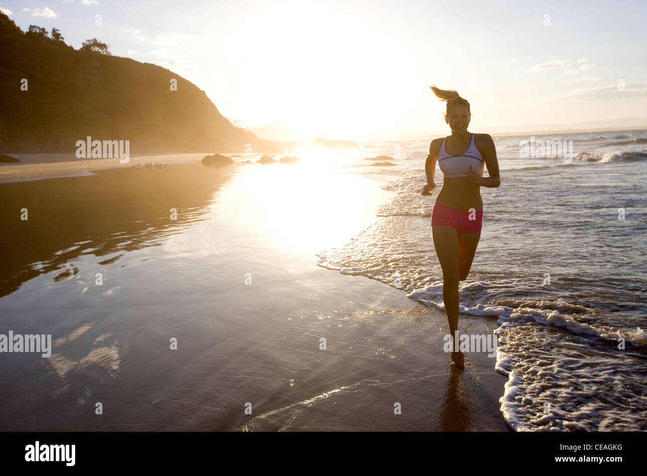 Girl exercising on the beach - Stock Image