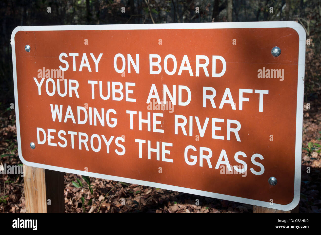 Stay on board your tube and raft. Wading the river destroys the grass. sign, Ichetucknee Springs State Park, Florida, - Stock Image