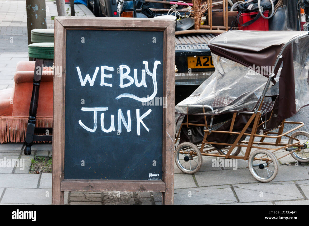 We Buy Junk sign on the pavement outside a junk shop in South London ...