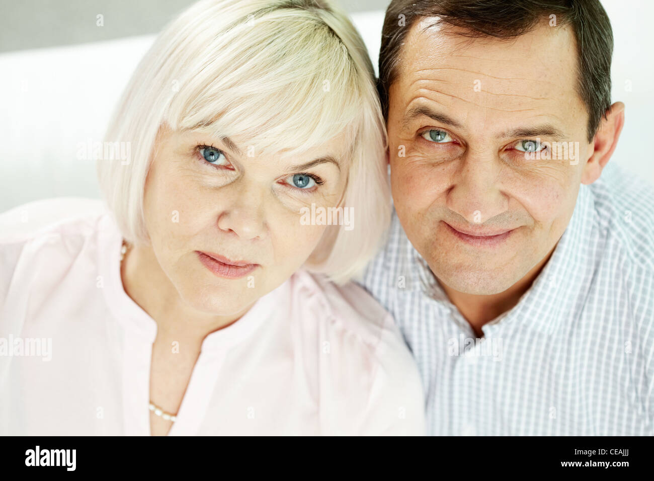 Portrait of mature woman and man looking at camera - Stock Image