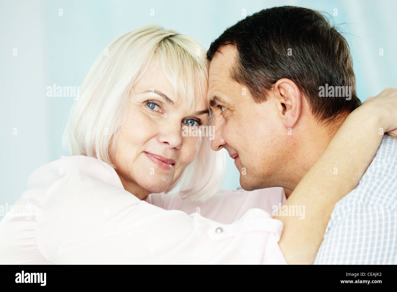 Portrait of mature woman looking at camera while embracing her husband - Stock Image