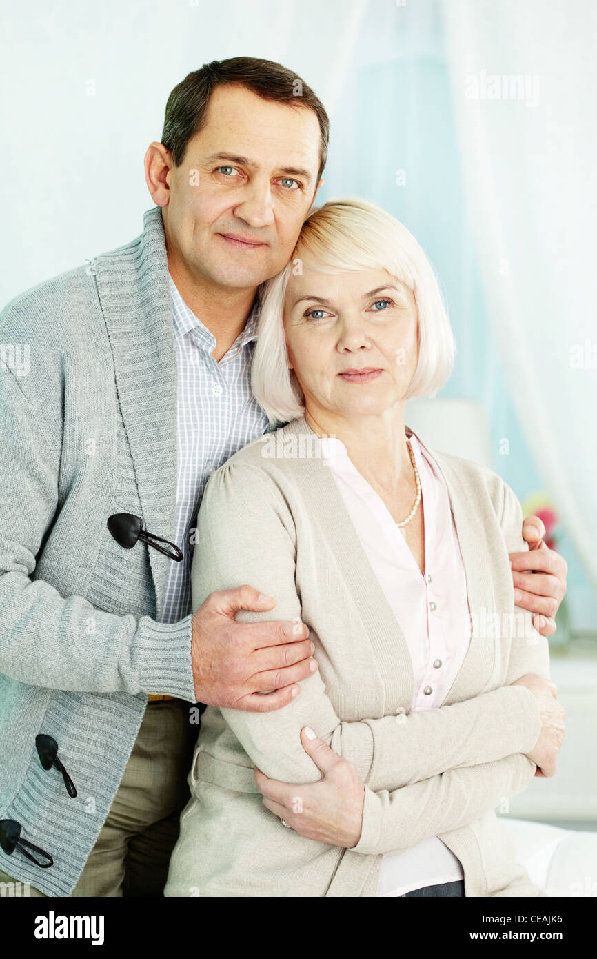 Portrait of a happy senior couple looking at camera and smiling - Stock Image
