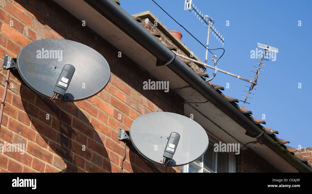 Satellite dishes TV aerials on houses - Stock Image