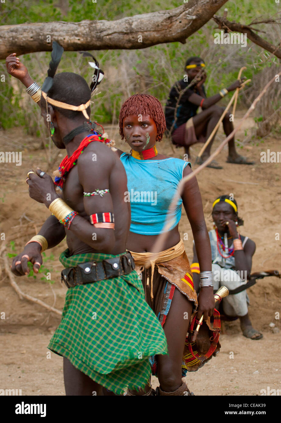 Great Whipper About To Flog Young Hamer Woman Celebrating Bull Jumping Ceremony Ethiopia - Stock Image