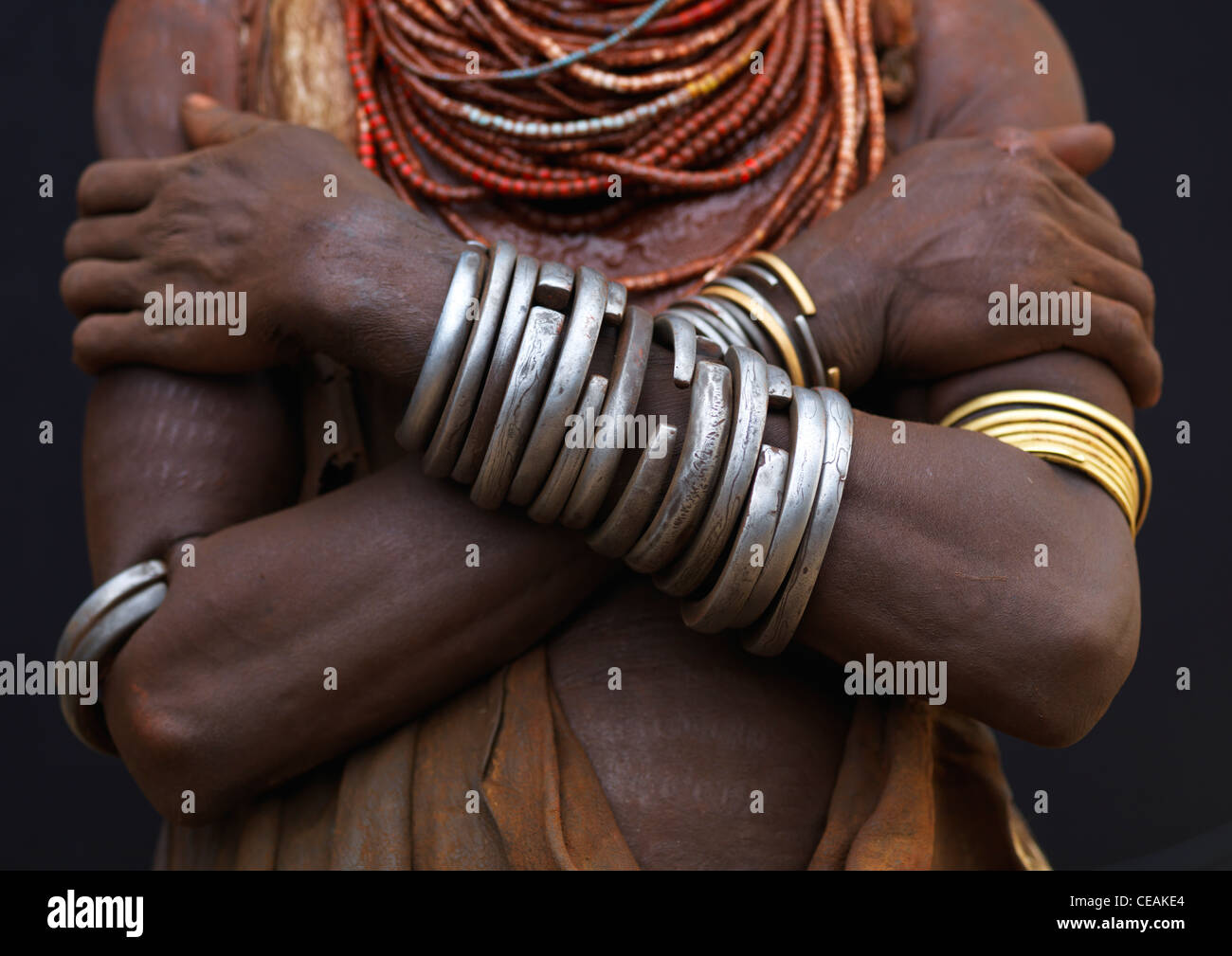Detail Of Karo Woman Chest Wearing Metal Bracelets And Beaded Necklaces, Crossed Arms Omo Valley Ethiopia - Stock Image