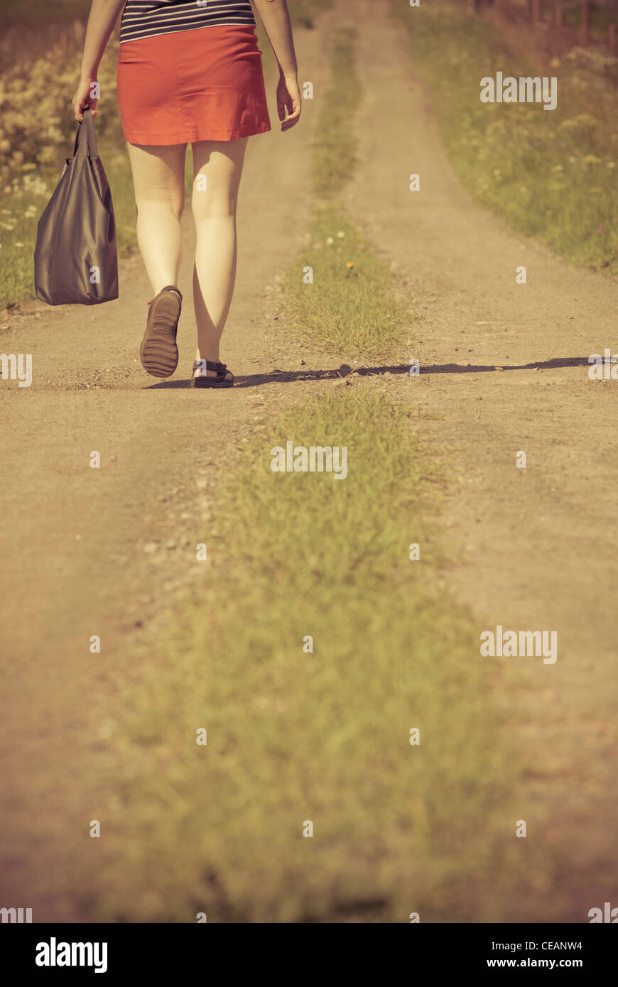 Woman walking on a dirt road - Stock Image