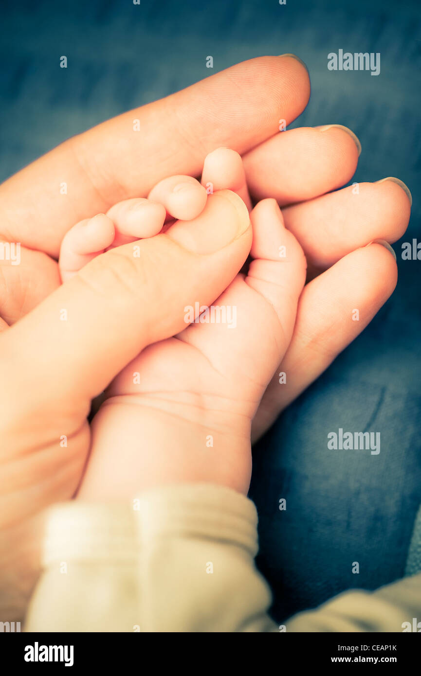 Mother holding hand of baby - Stock Image
