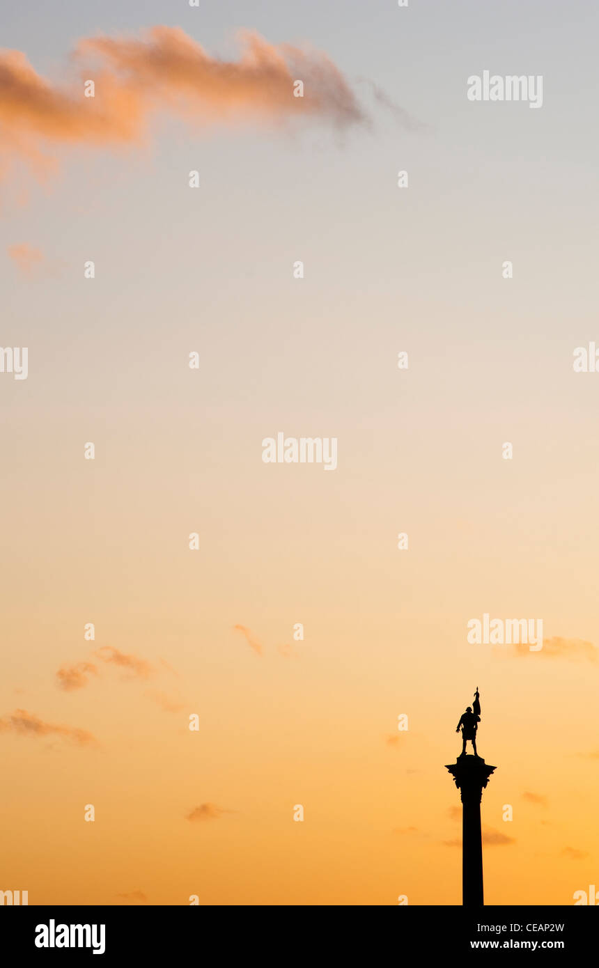 Statue on a pedestal and Orange Sky - Stock Image