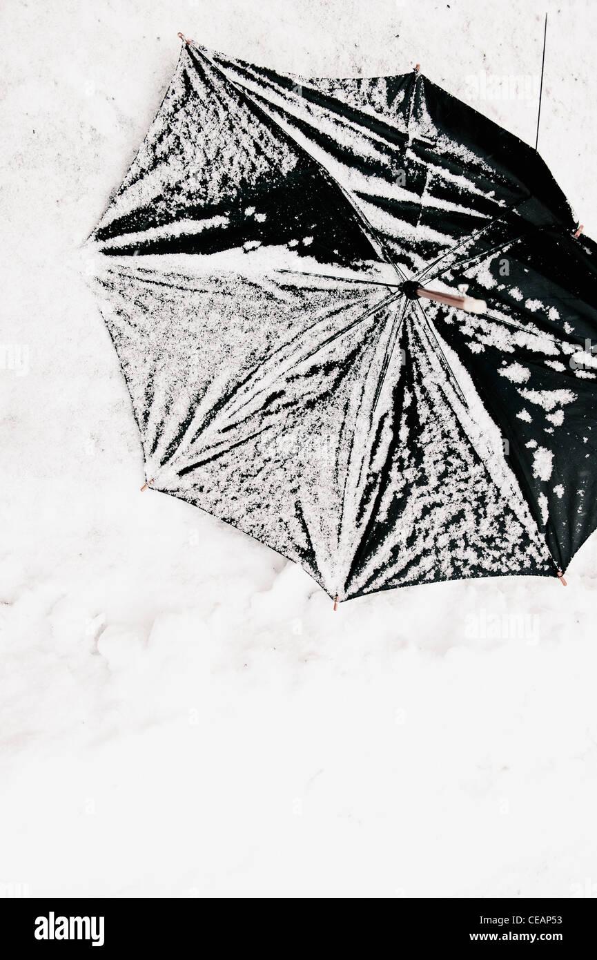 Broken umbrella in snow - Stock Image