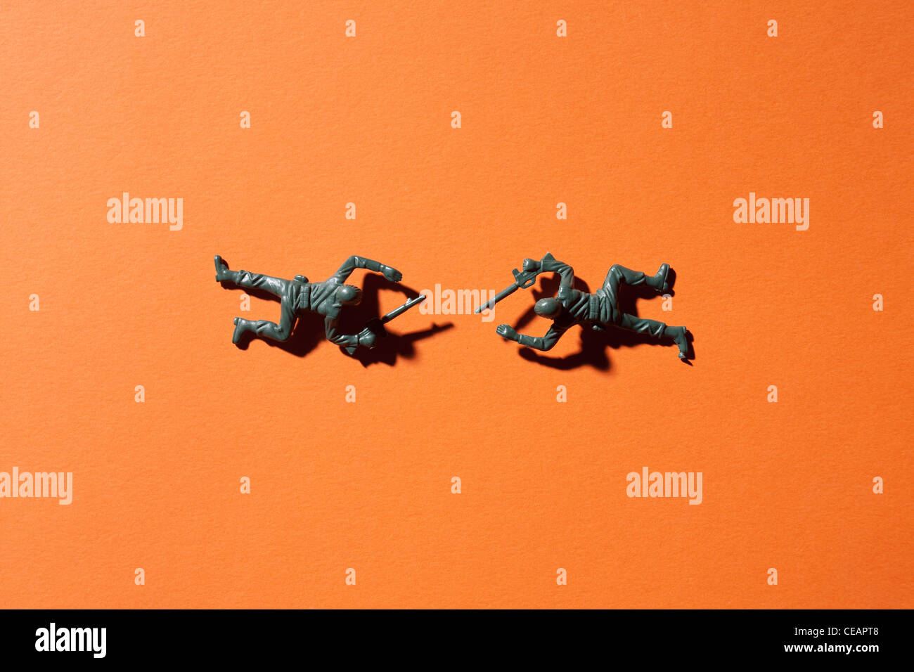 Two toy soldiers on orange background - Stock Image