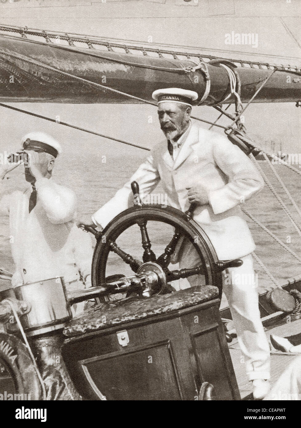 King George V at the wheel of his yacht, Britannia, during Cowes Regatta Week, England, 1924. - Stock Image