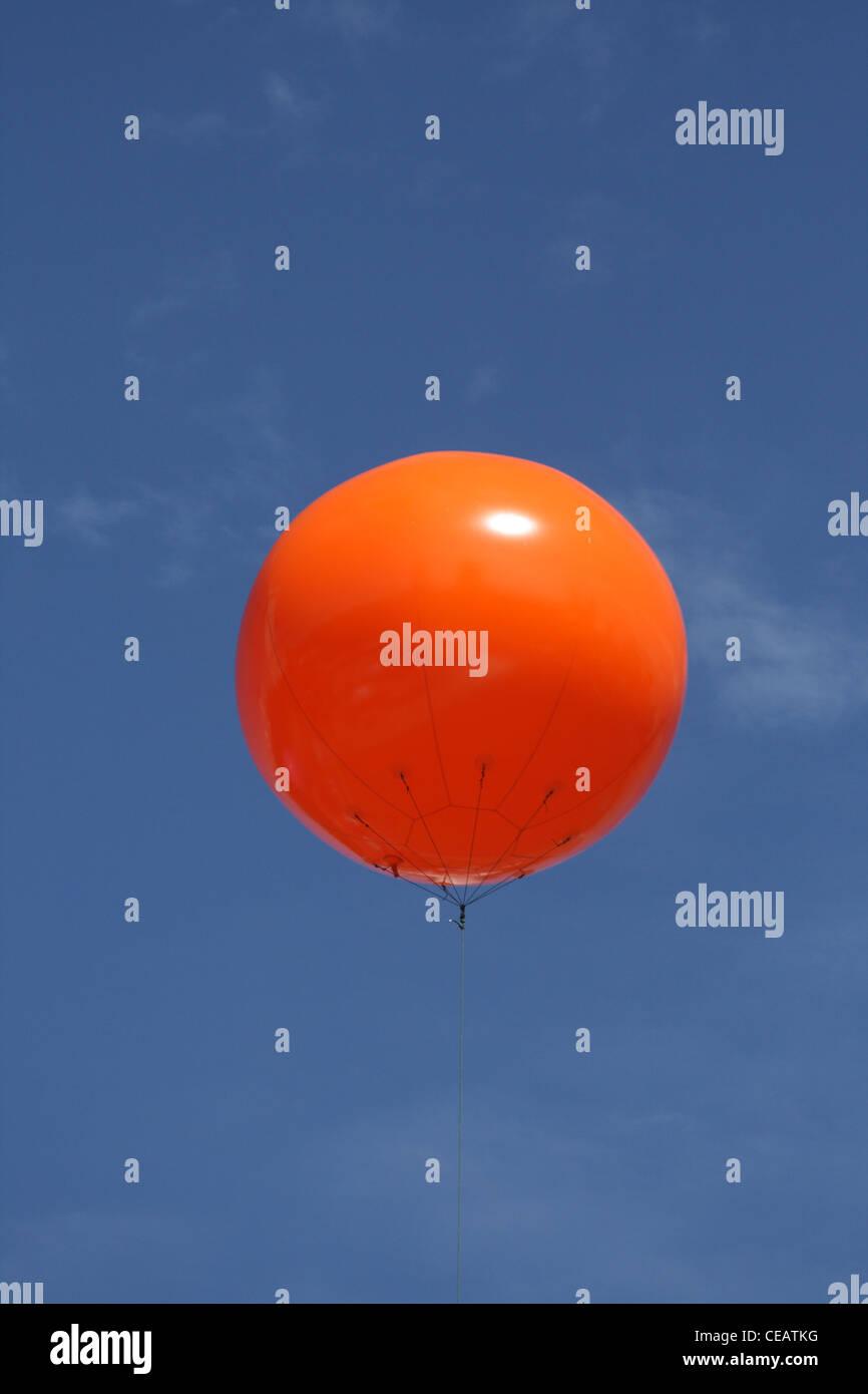 orange baloon floating against blue sky - Stock Image