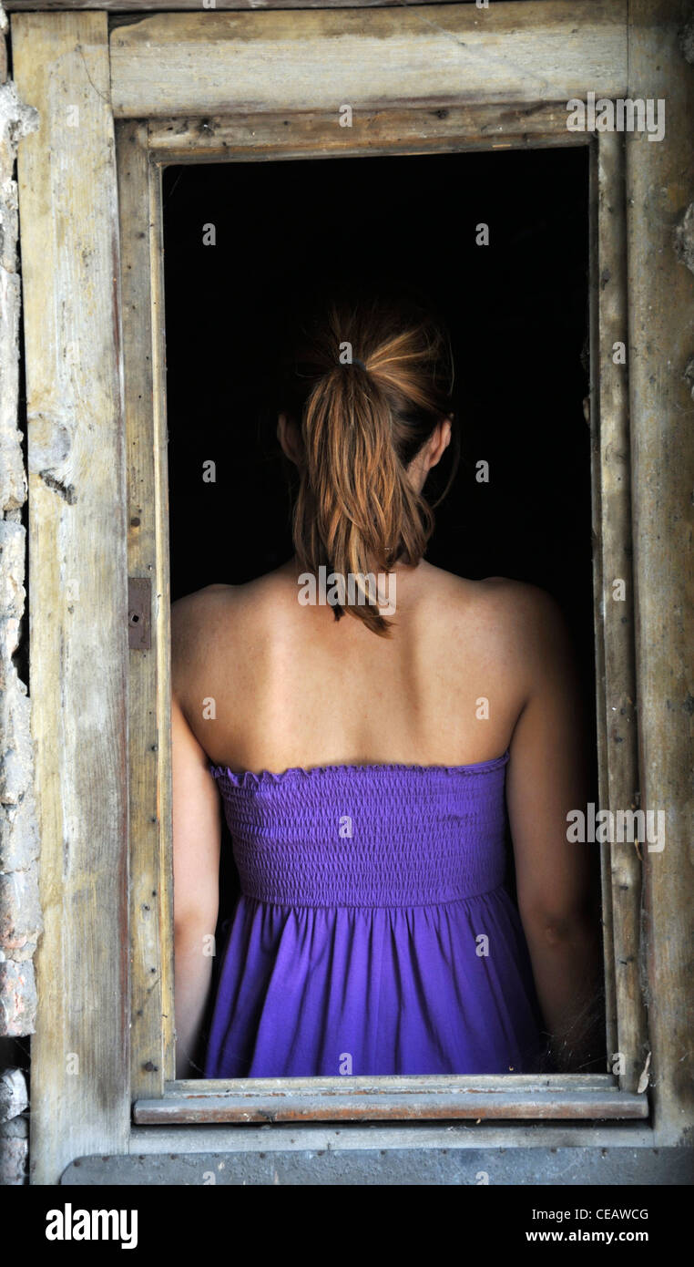 Young woman standing in window frame rear view - Stock Image