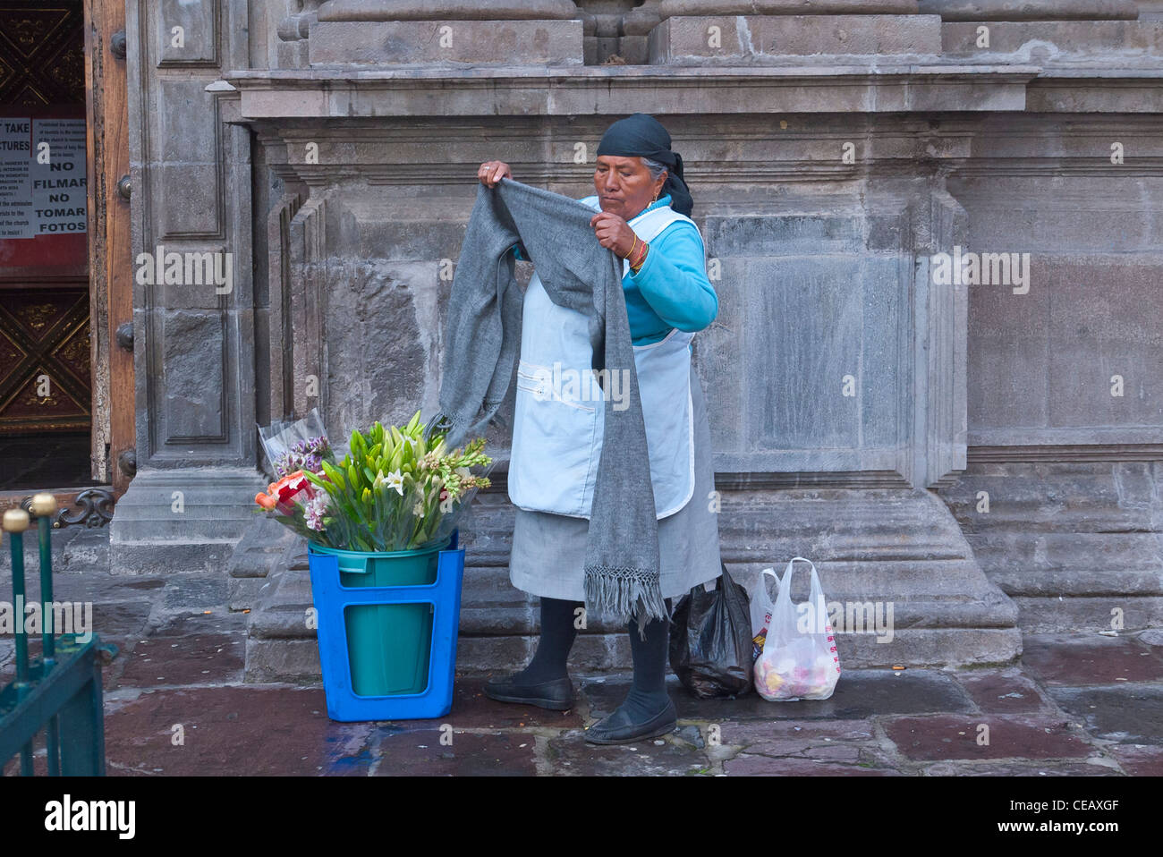 A 60-70 year old indigenous Indian woman prepares to sell her fresh flowers on the street outside a church in Quito, Ecuador. Stock Photo