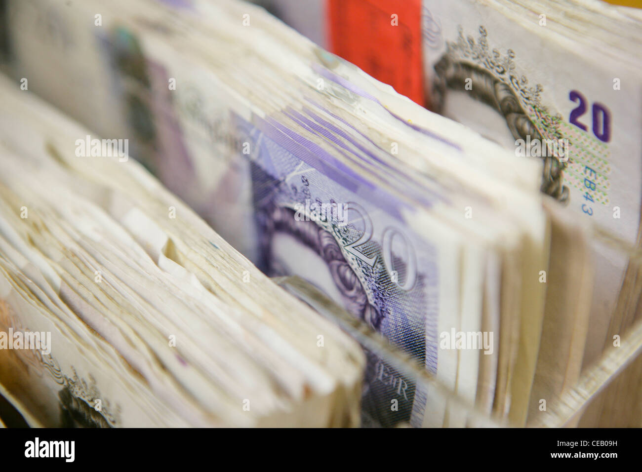 Ten and twenty pound notes in container - Stock Image