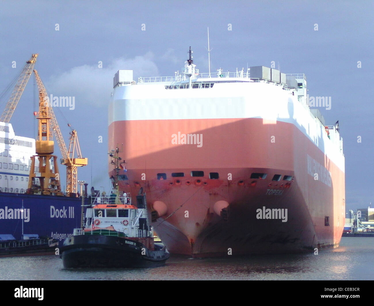 The car carrier Topeka is moving in the port of Bremerhaven. In front of the car carrier is the tugboat Bugsier - Stock Image