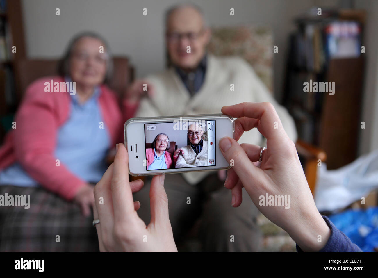 Using an iPhone 4S to take family photographs at home, different generations using intuitive touch screen technology, - Stock Image