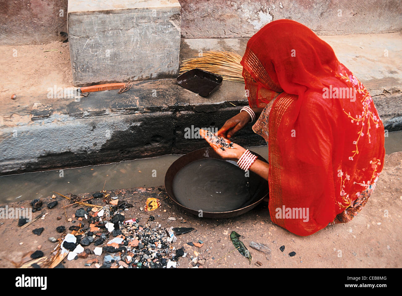 Woman looking for gold dust in a sewer ( India) - Stock Image