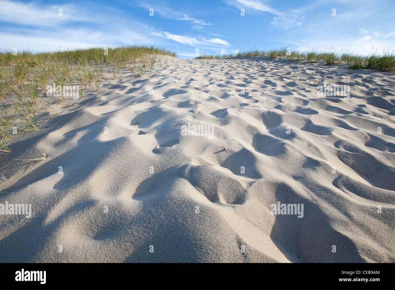 Footprints lead up steep sand dune - Stock Image
