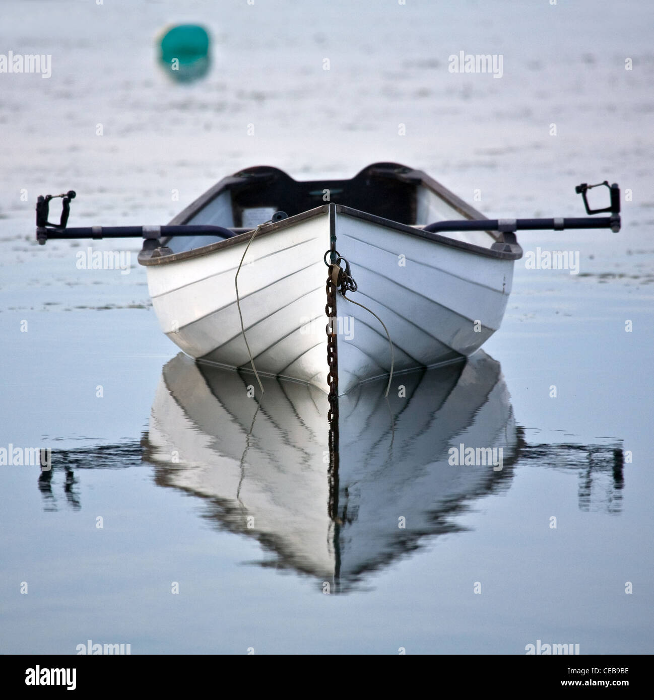 White wooden scull or row boat rests peacefully in water - Stock Image