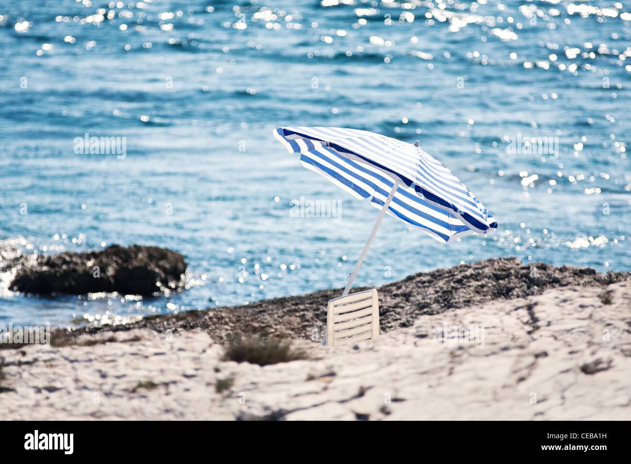 the stony beach with parasol - Kamenjak near Premantura, 13 km by Pula - Stock Image