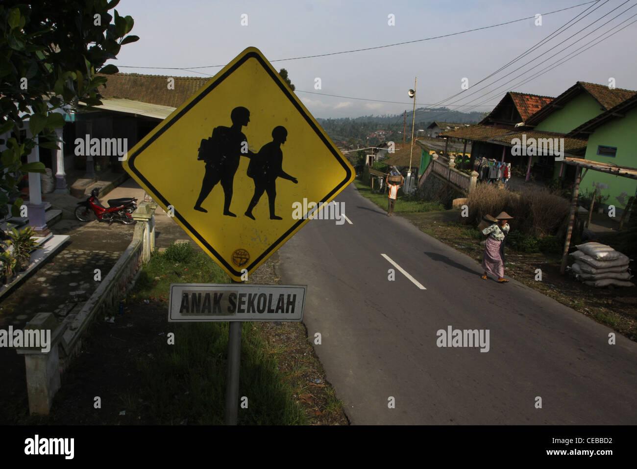 sign reading school children women carrying food village road Yogyakarta Indonesia - Stock Image