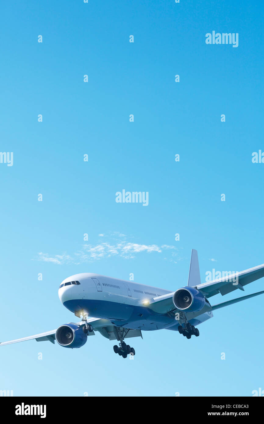 Jet plane in a clear blue sky. Vertical composition. - Stock Image