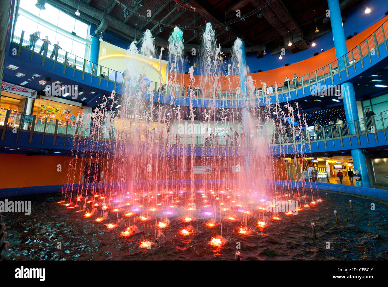 Brightly colored dancing water fountain display in a shopping mall with shoppers enjoying the show. - Stock Image