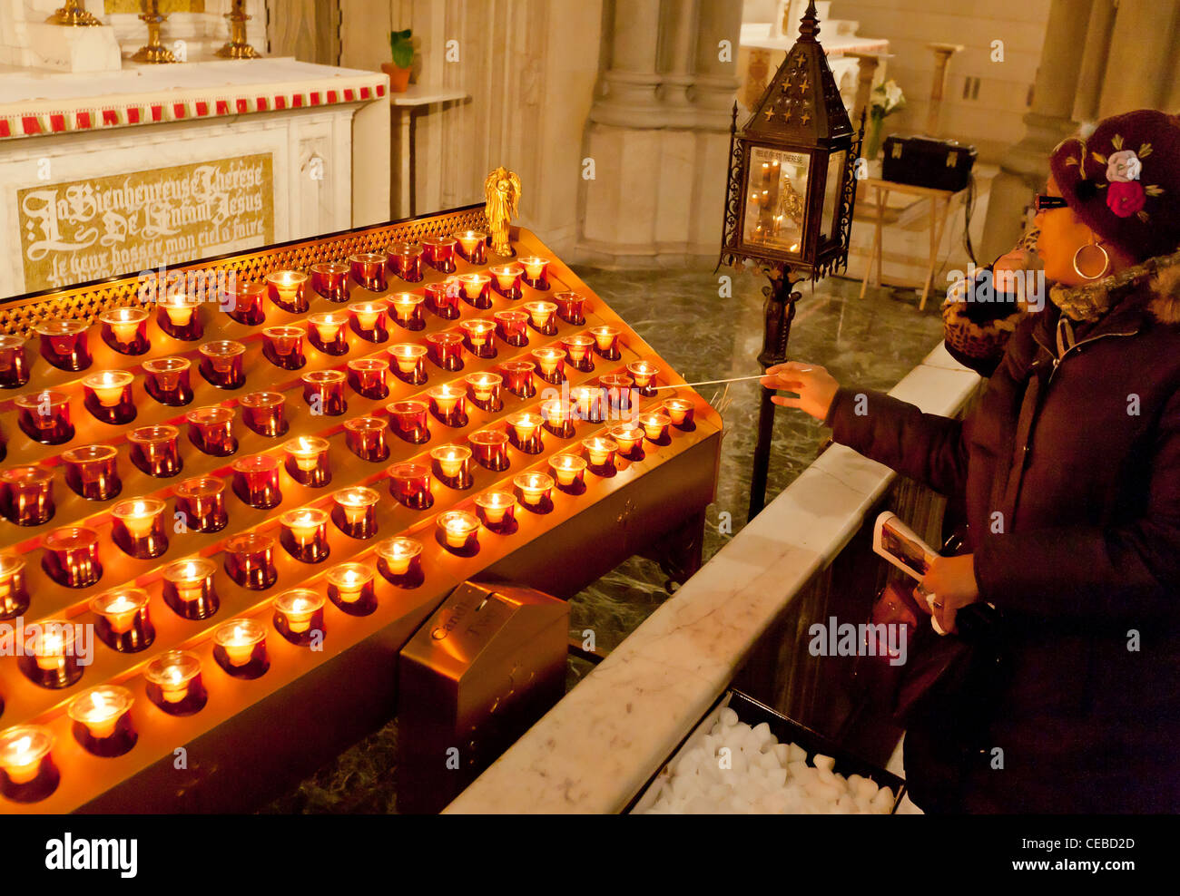 A person lights a candle in a church. - Stock Image