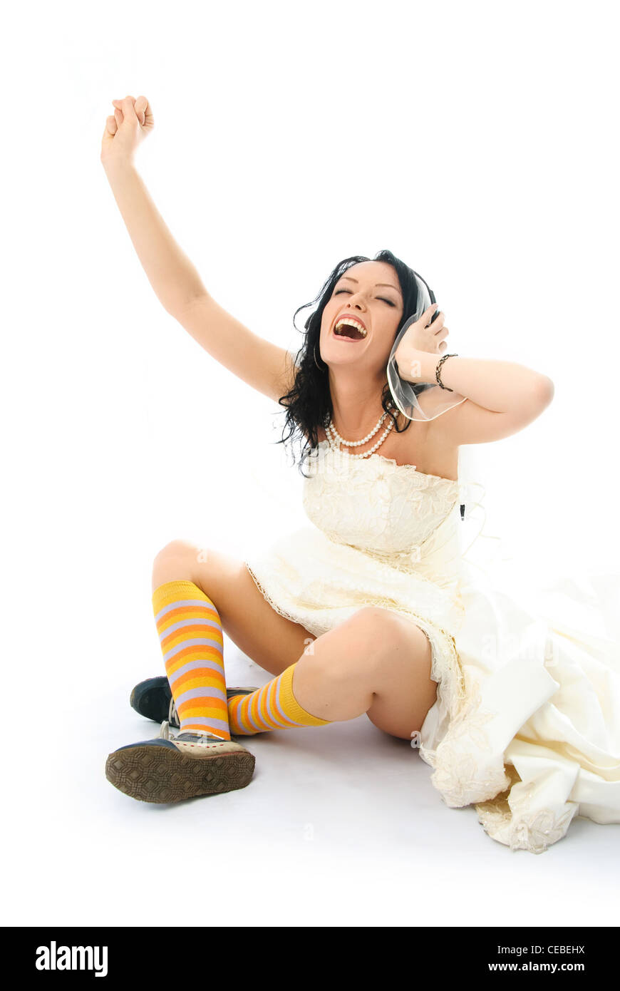 happy young brunette bride wearing sporting shoes and listening to the music Stock Photo