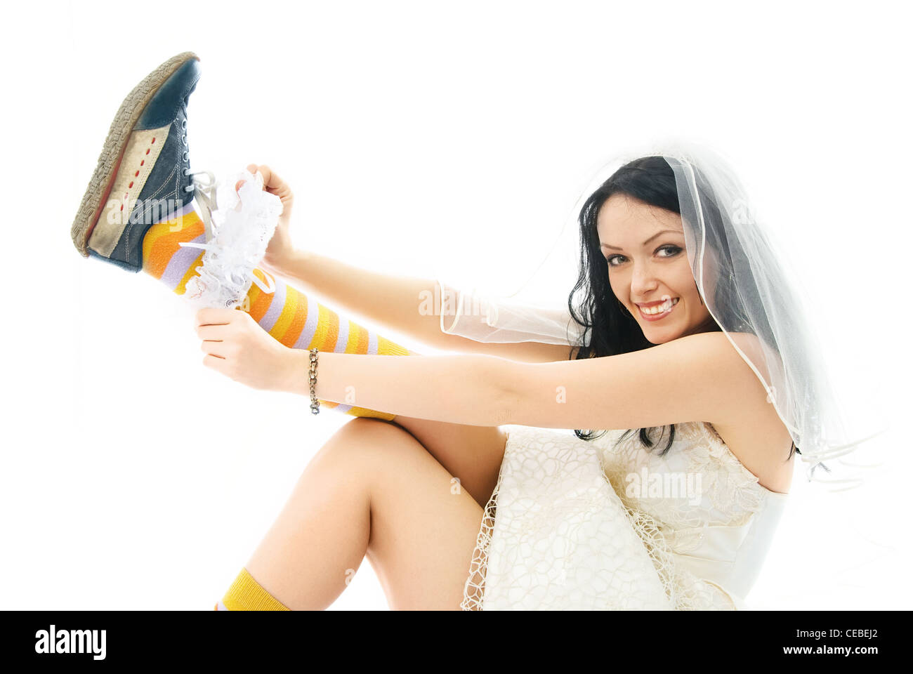 funny young bride wearing sporting shoes puts on a garter and smiles Stock Photo