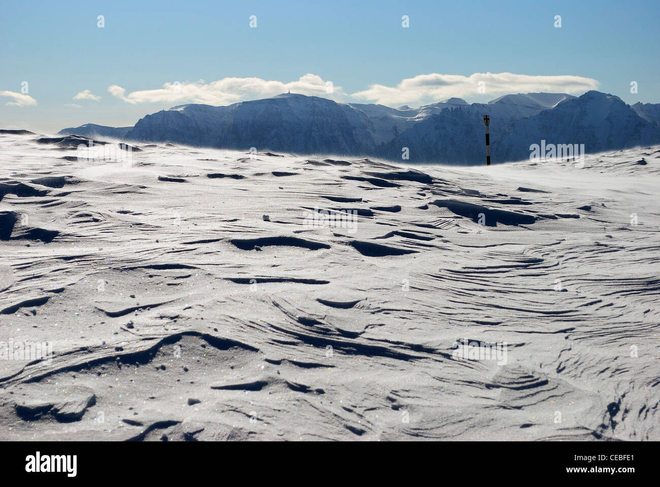Snowy landscape with mountains in the background with some clouds. - Stock Image