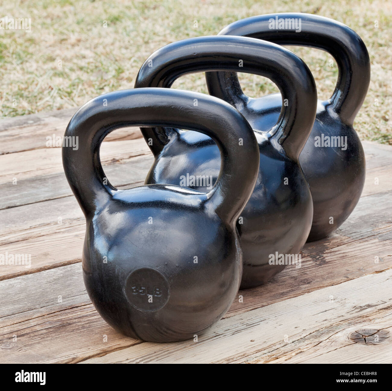 three black iron kettlebell for weight training (35 and 50 lb) on wood grunge deck, outdoors with sky reflections - Stock Image