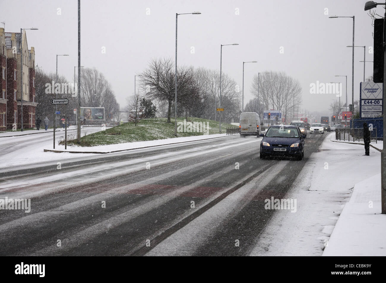Cars and people in snowfall along Hyde Road - looking towards Reddish - Stock Image