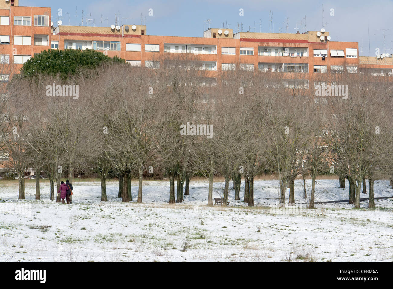 City park and apartment buildings under the snow, with two persons on a path, Rome - Stock Image
