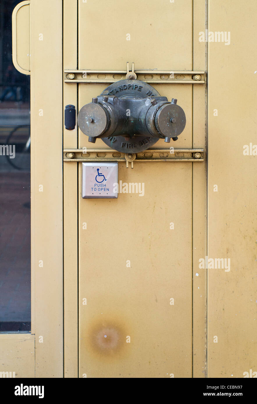 Curious juxtaposition of dry standpipe connection points and a disabled access push switch to open a door in San - Stock Image