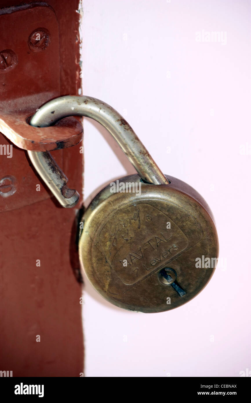 An Old Rusted Lock Hanging On The Hook In Door Wall