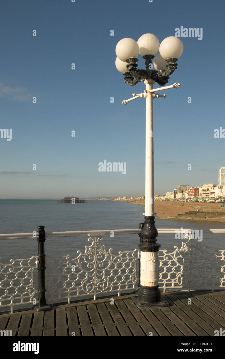 The view west from Brighton Pier with the remains of the West Pier in the background. - Stock Image
